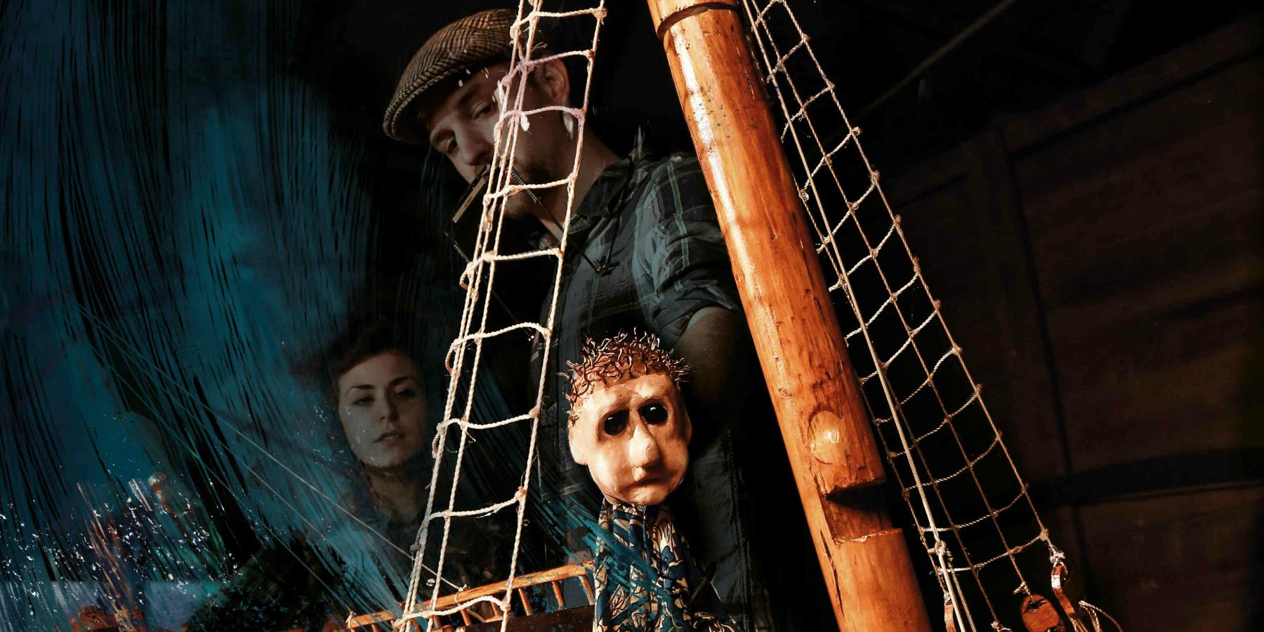 A puppet on a wooden ship, the sea spraying onto deck, the puppeteers in the background